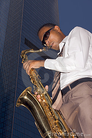 Jugador de saxofón urbano en fondo del rascacielos