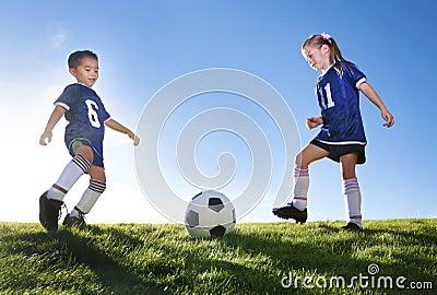 Jugadores de fútbol jovenes que golpean la bola con el pie