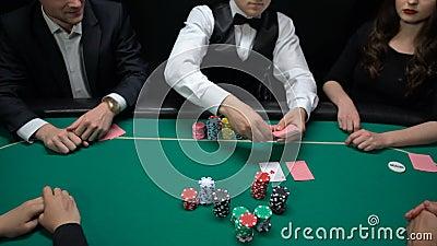 Jugadores que apuestan y distribuidor autorizado del póker que da vuelta encima de tarjetas de la comunidad a la tabla del casino metrajes