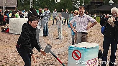 Jugendlich und Mädchen stoßen Sie schwach auf empfindlichem aufblasbarem bereitstehen Schmiedehammer Sommerfestival stock footage
