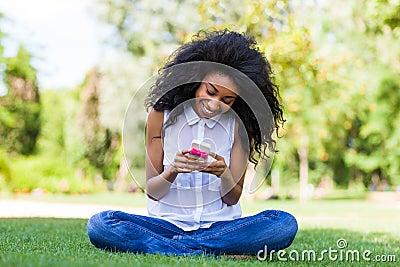 Jugendliches schwarzes Mädchen, das ein Telefon, liegend auf dem Gras - afrikanisches p verwendet