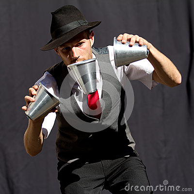 Juggler playing with three cups. Editorial Stock Photo