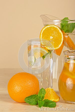 Jugs with drinks, oranges and spearmint