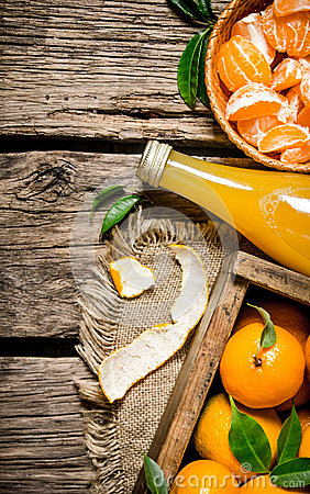 Free Juice In A Bottle, A Box Of Mandarins And Tangerines, Spooned Into The Cup. Royalty Free Stock Images - 64524649