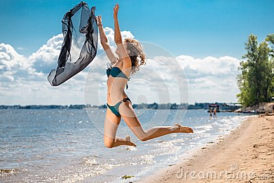 Jumping happy girl on the beach, fit sporty healthy sexy body in bikini