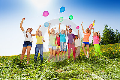 Jumping kids with flying balloons in summer