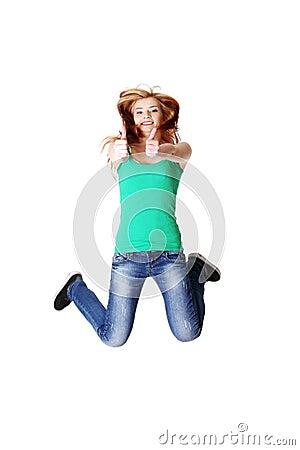 Jumping teen student showing okay gesture