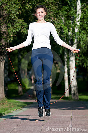 Jumping woman with skipping rope at park