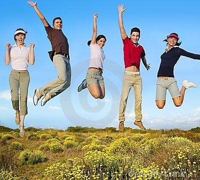 Jumping young people happy group on yellow flowers