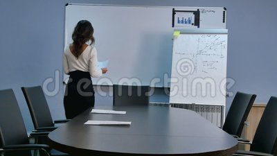 Junge asiatische Sekretärin bereitet Sitzungssaal vor und stellt Papiere auf ihren Schreibtisch stock video