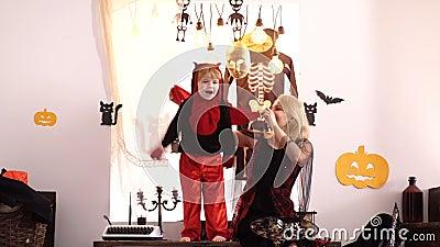 Junge auf Halloween-Party in Kostümen Klein Kind in Drachenkostüme mit seiner Mutter feierliches Halloween-Karneval stock footage