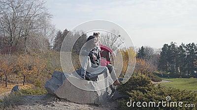 Junge blonde kaukasische Frau, die mit ihrem Hippie-Freund aus dem Nahen Osten auf Felsen sitzt und spricht Glückliches Paar ruht stock video