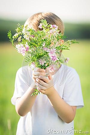 Junge, der durch Blumenstrauß sich versteckt