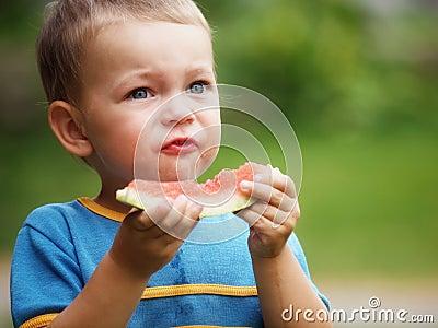 Junge, der Melone isst