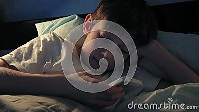 Junge, der in seinem Bett am Abend stillsteht und sein intelligentes Telefon verwendet stock video