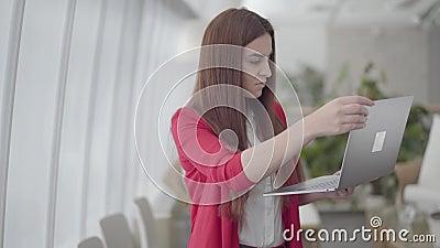 Junge Frau in der roten Klage schreibend auf ihrem Gerät im modernen hellen Büro Das Mädchen schließt ihr netbook und Lächeln b?r stock footage