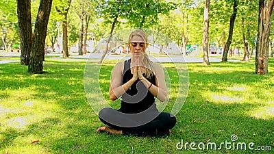 Junge Frau des breiten Schusses, die Yoga im Park tut stock video