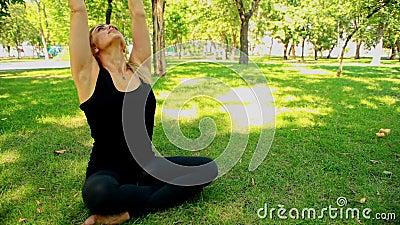 Junge Frau des breiten Schusses, die Yoga im Park tut stock footage