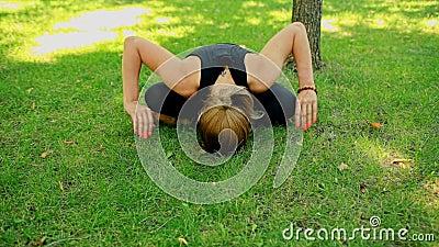 Junge Frau des mittleren Schusses, die Yoga im Park tut stock video footage