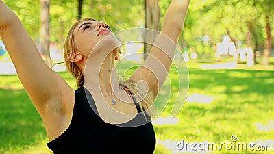 Junge Frau des mittleren Schusses, die Yoga im Park tut stock footage