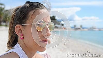 Junge Frau, die auf einem Strand herein schaut zum Abstand sitzt stock footage