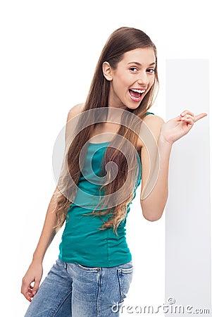 Junge Frau, die auf unbelegtes Plakat zeigt