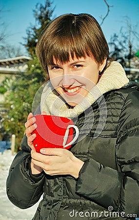 Junge Frau, die draußen heißen Tee trinkt