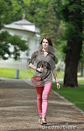 Junge Frau, die in einen Park geht