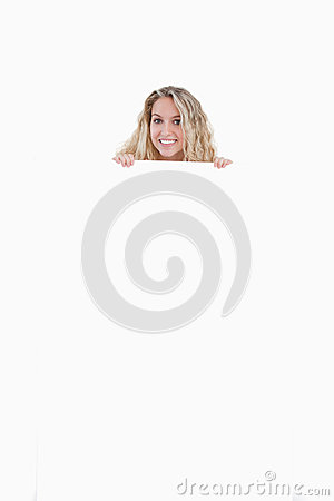Junge Frau, die ihre Karosserie hinter einem unbelegten Plakat versteckt