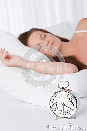 Junge Frau, die im Bett mit Alarmuhr schläft