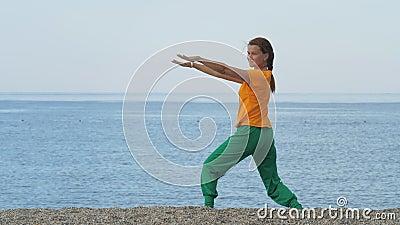 Junge Frau, die sich auf einem Sandstrand vor dem Hintergrund des Meeres oder Ozeans ausstreckt stock video footage