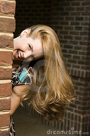 Junge Frau, die um Ecke sich versteckt