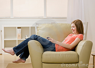 Junge Frau, die zum MP3-Player auf Lehnsessel hört