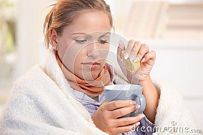 Junge Frau fing kaltes trinkendes Teegefühlsschlechtes ab