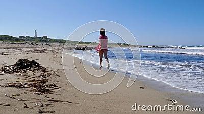 Junge Frau im roten Kleid, das entlang den leeren Strand läuft Starke Wellen spritzen und wickeln den Schlag Leuchtturm auf dem H stock footage