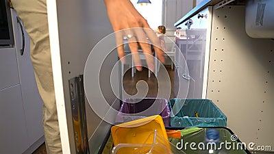 Junge Frau lässt den Abfall in Küchen-Wiederverwertungs-Behälter fallen transportwagen stock footage
