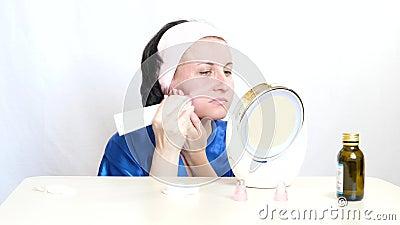 Junge Frau mit einem Gerät führt microdermabrasion der Haut des Gesichtes auf einem weißen Hintergrund durch Das Konzept von stock video footage
