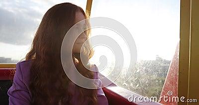 Junge Frau mit lockig langen roten Haaren sitzt bei Sonnenuntergang in der Standseilbahn oder in der Fäulnisradkabine stock video