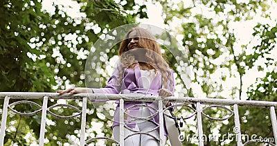 Junge Frau mit lockig langen roten Haaren streift auf einer Gehbrücke im Sommerpark und freut sich auf die Zukunft stock video footage