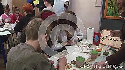 Junge Frau zwei, die jugendlich Jungen hilft, durch Wattestäbchen bei Tisch zu zeichnen festival kreation Geschenk mit Liebe stock video footage
