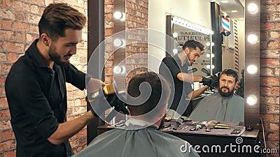 Junge Friseurin mit Haarschneidemaschine und Friseurin-Klient im Friseursalon stock footage