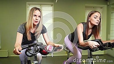 Junge geeignete Frauen, die auf Standrad in der Turnhalle radfahren stock video
