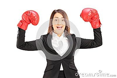 Junge Geschäftsfrau mit roten Boxhandschuhen Erfolg gestikulierend