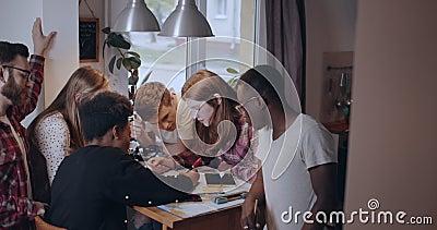 Junge, glücklich fokussierte, multiethnische Schülerfreunde studieren gemeinsam mit Küchentisch mithilfe von Big-Map-Daten Zeitlu stock video