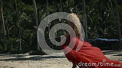 Junge glückliche Frau mit lockig blonden Haaren in elegantem, langes Rot stock video