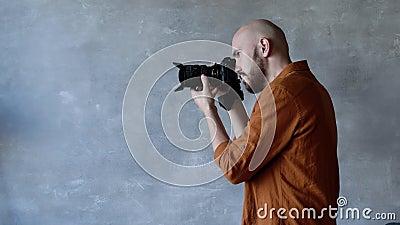 Junge, gut aussehende Fotografen mit Bart, die im Studio auf einer professionellen Kamera fotografieren Rückstau stock video