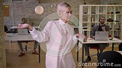 Junge hübsche Geschäftsfrau tanzt in Büro, Kollegen klatschen, bearbeiten Konzept, sich entspannen Konzept stock video footage
