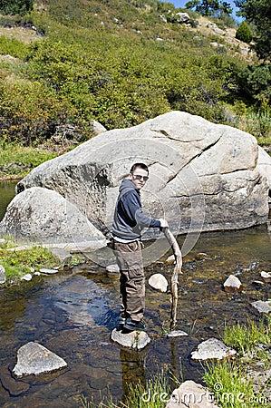 Junge im Fluss durch einen Fluss-Stein