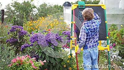 Junge Künstlerin zieht Vorstand Ein Junge unter den Blumen und Pflanzen im Freien zeichnet Kinderbilder mit stock video footage