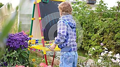 Junge Künstlerin zieht Vorstand Ein Junge unter den Blumen und Pflanzen im Freien zeichnet Kinderbilder mit stock video
